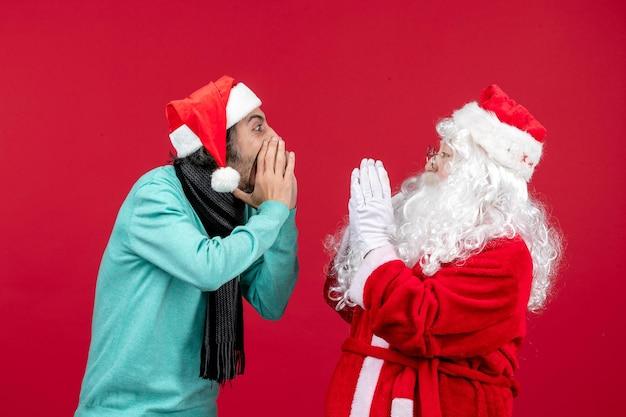 Vooraanzicht kerstman met man die met elkaar in wisselwerking staat op rode kerstmis