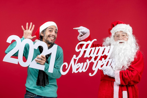 Vooraanzicht kerstman met mannelijke holding en gelukkig nieuwjaar schrijven op rode nieuwjaarskerst