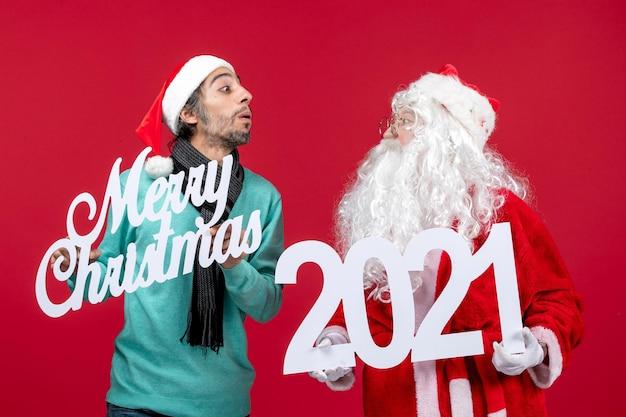 Vooraanzicht kerstman met mannelijke holding en vrolijke kerstgeschriften op rode kerstcadeaus