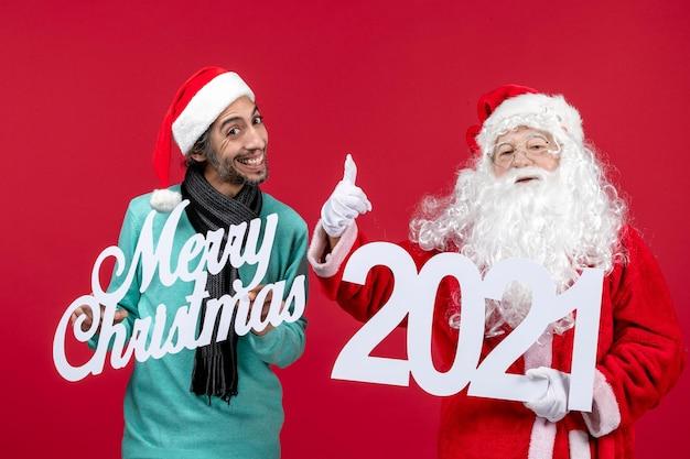 Vooraanzicht kerstman met mannelijke holding en vrolijke kerstgeschriften op rode nieuwjaarskerstmis
