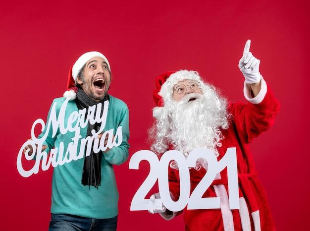 Vooraanzicht kerstman met mannelijke holding en vrolijke kerstgeschriften op rood heden nieuw jaar