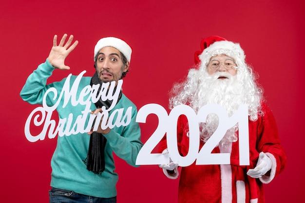 Vooraanzicht kerstman met mannelijke holding en vrolijke kerstgeschriften over rode kerstemotie nieuwjaar