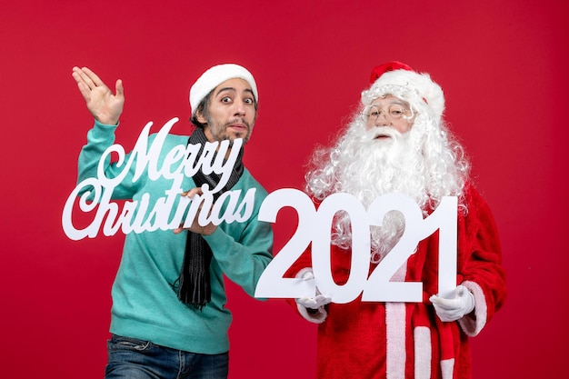 Vooraanzicht kerstman met mannelijke holding en vrolijke kerstgeschriften over rode kerstemotie