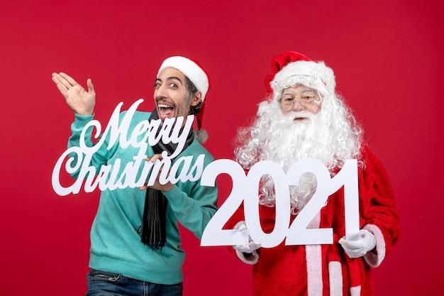 Vooraanzicht kerstman met mannelijke holding en vrolijke kerstgeschriften over rode kerstemoties