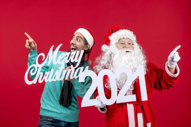 Vooraanzicht kerstman met mannelijke holding en vrolijke kerstgeschriften over rode kerstkleurvakantie