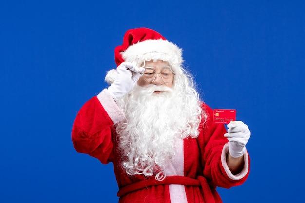 Vooraanzicht kerstman met rode bankkaart op blauwe nieuwjaarskleuren vakantie kerstcadeau