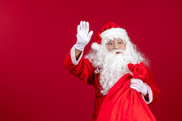 Vooraanzicht kerstman met rode tas vol cadeautjes groet op rode kerst