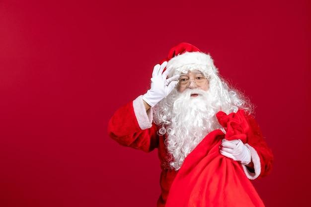 Vooraanzicht kerstman met rode tas vol cadeautjes op rode kerst nieuwjaarsvakantie