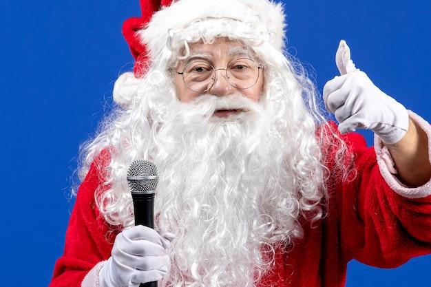Vooraanzicht kerstman met rood pak en witte baard met microfoon op blauwe kleur vakantie kerstmis nieuwjaar