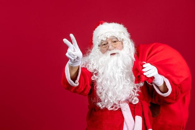 Vooraanzicht kerstman met tas vol cadeautjes op rode feestdagen nieuwjaar kerstemotie