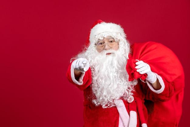 Vooraanzicht kerstman met tas vol cadeautjes op rood bureau vakantie nieuwjaar kerstemotie