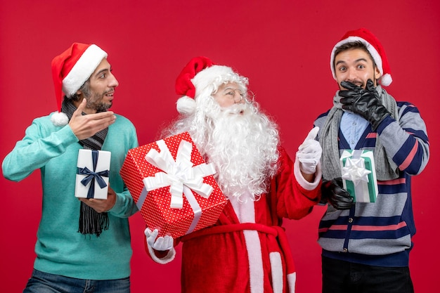 Vooraanzicht kerstman met twee mannen die cadeautjes vasthouden op rode nieuwjaarscadeau-emoties kerstrood