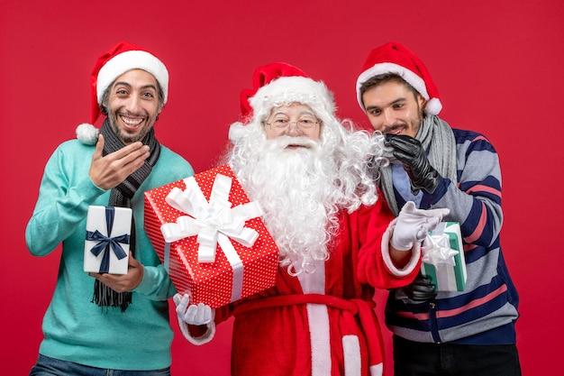 Vooraanzicht kerstman met twee mannen die cadeautjes vasthouden op rood rood nieuwjaar cadeau emotie kerstmis
