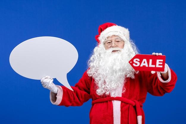 Vooraanzicht kerstman met verkoop en groot wit bord op blauwe kleur sneeuwvakantie nieuwjaar kerstmis