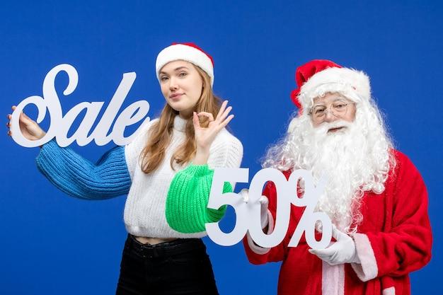 Vooraanzicht kerstman met vrouw die verkoopgeschriften vasthoudt over blauwe vakanties koud kerstmis nieuwjaar sneeuw winkelen