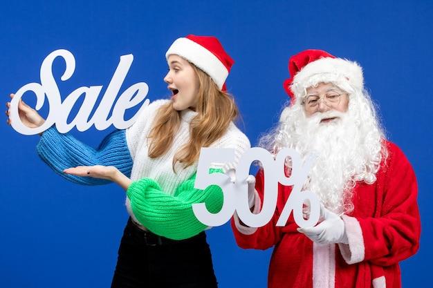 Vooraanzicht kerstman met vrouwelijke verkoopgeschriften op de blauwe vakantie koude kerstmis nieuwjaarssneeuw