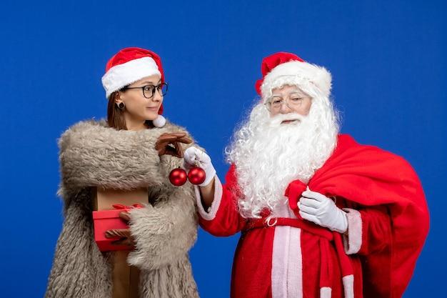 Vooraanzicht kerstman samen met jonge vrouw op blauwe menselijke xmas kleur nieuwjaar