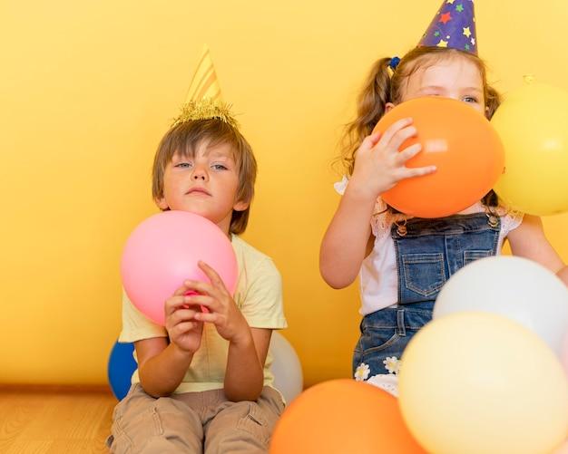 Vooraanzicht kinderen spelen met ballonnen binnenshuis