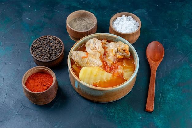 Vooraanzicht kippensoep met aardappelen samen met zout peper kruiden op het donkerblauwe oppervlak soep vlees eten diner maaltijd