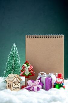 Vooraanzicht kladblok speelgoed kleine geschenken mini kerstboom mini houten huis op groen geïsoleerd oppervlak