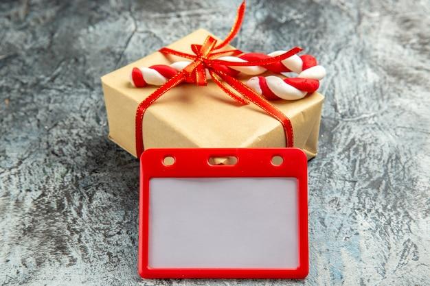 Vooraanzicht klein cadeau gebonden met rood lint xmas candy kaarthouder op grijs