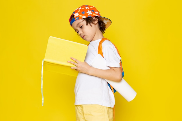 Vooraanzicht klein kind in wit t-shirt schrift lezen op gele verdieping