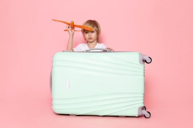 Vooraanzicht klein kind jongen blonde haren spelen met speelgoed oranje vliegtuig op het roze bureau