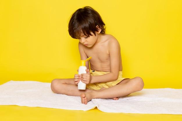Vooraanzicht klein kind met behulp van crème op gele vloer