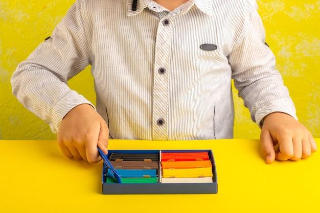 Vooraanzicht klein kind spelen met gekleurde plasticines op geel oppervlak