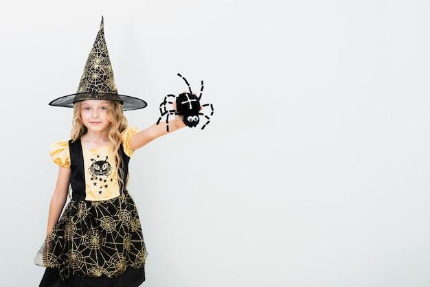 Vooraanzicht klein meisje in heks kostuum met kopie ruimte