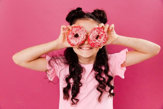 Vooraanzicht klein meisje spelen met doughntus