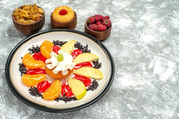 Vooraanzicht kleine cake met gesneden fruit en rozijnen op witte achtergrond, zoete koekjes, suikervruchten, koekjescake