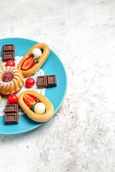 Vooraanzicht kleine cake met zoete crackerschocolade en aardbeien op een witte achtergrond, zoete koekjestaart, fruitkoekjescake