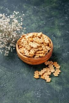 Vooraanzicht kleine crackers in plaat op donkergrijze achtergrond knapperige snack zout brood beschuit voedsel cips kleur