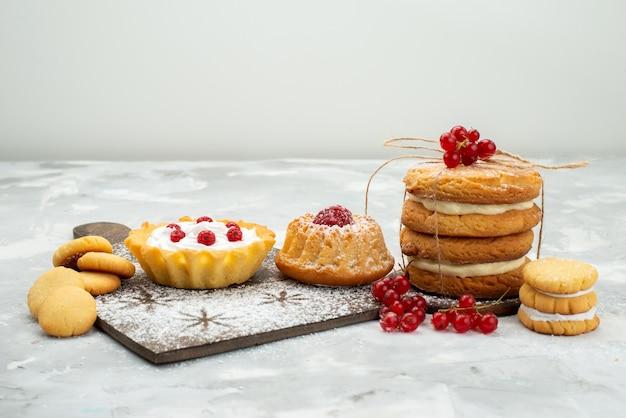 Vooraanzicht kleine d cakes met room en sandwichkoekjes op het lichte zoete suiker van het oppervlak