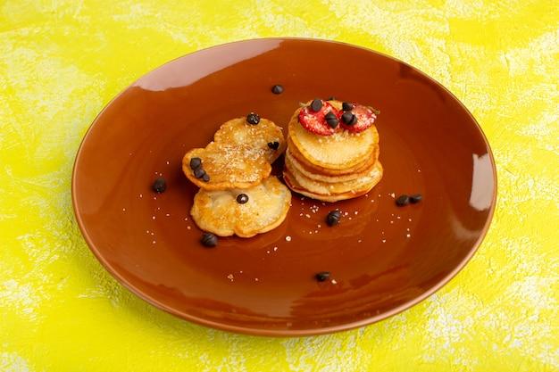 Vooraanzicht kleine gebakken gebakjes met gedroogde vruchten op de gele tafel, fruit berry zoete suiker gebak
