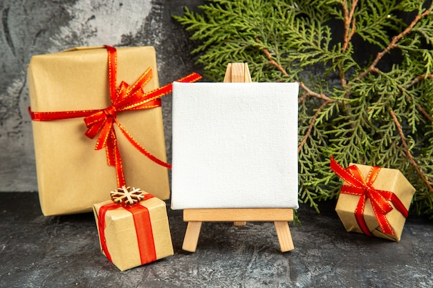 Vooraanzicht kleine geschenken gebonden met rood lint mini canvas op houten ezel dennentak op grijze achtergrond