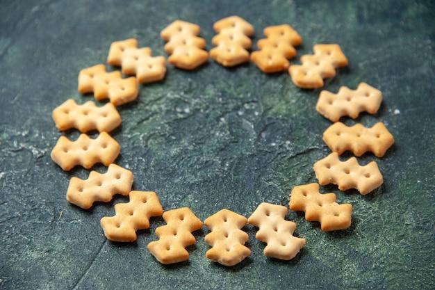 Vooraanzicht kleine gezouten crackers in cirkelvorm op donkere achtergrond knapperige kleur snack cips zout brood droog beschuit voedsel peper