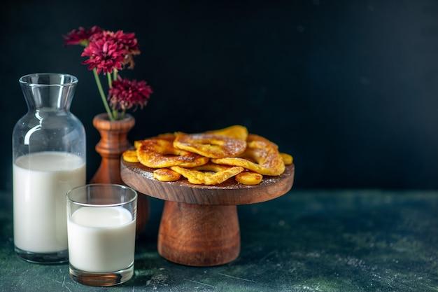 Vooraanzicht kleine heerlijke taarten in de vorm van een ananasring met melk op het donkere oppervlak