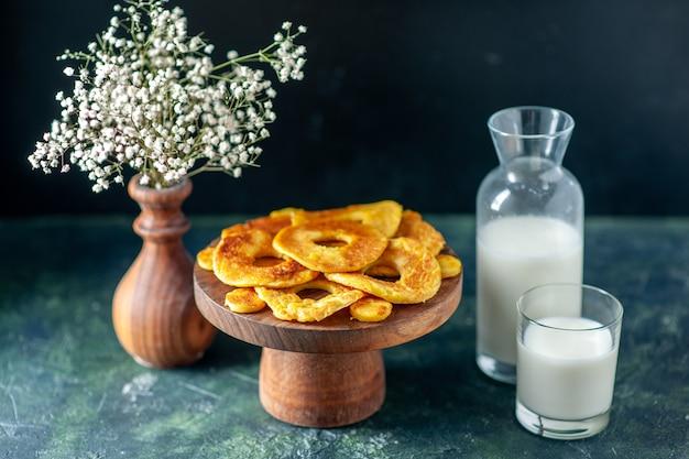 Vooraanzicht kleine heerlijke taarten in de vorm van een ananasring op donkere fruittaartgebaktaart, hotcake-kleurbak