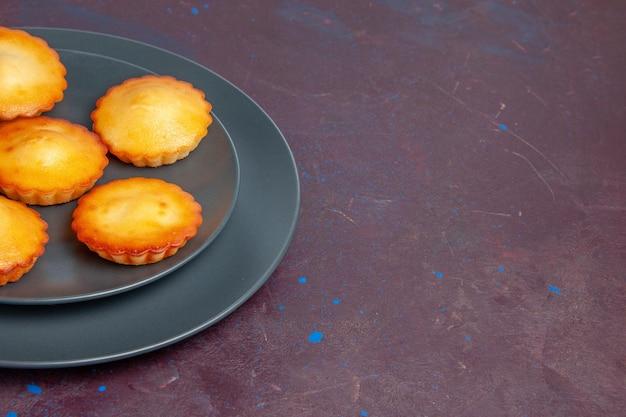 Vooraanzicht kleine heerlijke taarten in plaat op donkere achtergrond taart biscuit cake zoete koekjes suiker thee
