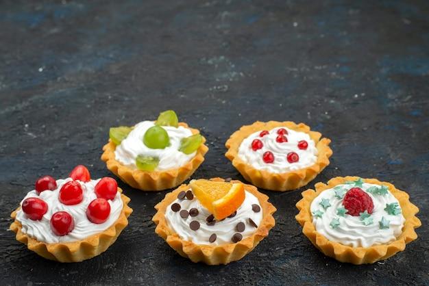 Vooraanzicht kleine heerlijke taarten met room en vers fruit op het donkere oppervlak zoete koektaart suiker thee