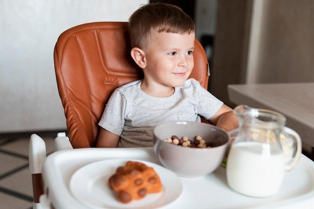 Vooraanzicht kleine jongen met assortiment snacks