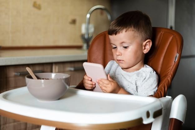 Vooraanzicht kleine jongen met behulp van een telefoon