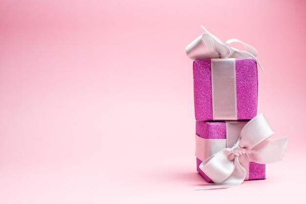 Vooraanzicht kleine kerstcadeautjes op roze kerstkleur cadeau foto nieuwjaar vakantie vrije ruimte