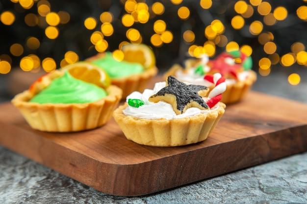 Vooraanzicht kleine kersttaartjes op snijplank op donkere geïsoleerde oppervlak kerstverlichting