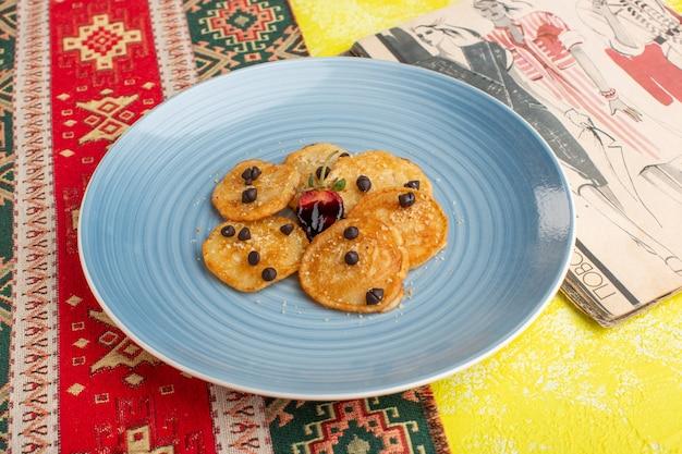 Vooraanzicht kleine koekjesgebakjes in blauwe plaat op de gele tafel, bak zoet theegebak
