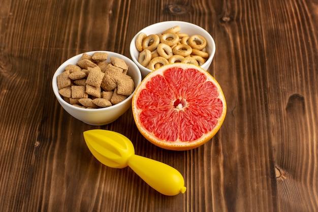 Vooraanzicht kleine kussenkoekjes met crackers en grapefruit op bruin bureau