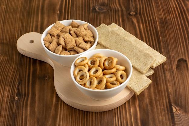Vooraanzicht kleine kussenkoekjes met crackers op het bruine bureau