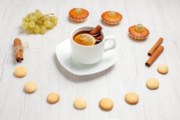 Vooraanzicht kleine lekkere taarten met druiven, kopje thee en koekjes op wit bureau, fruitcake, koekje, zoete dessertthee